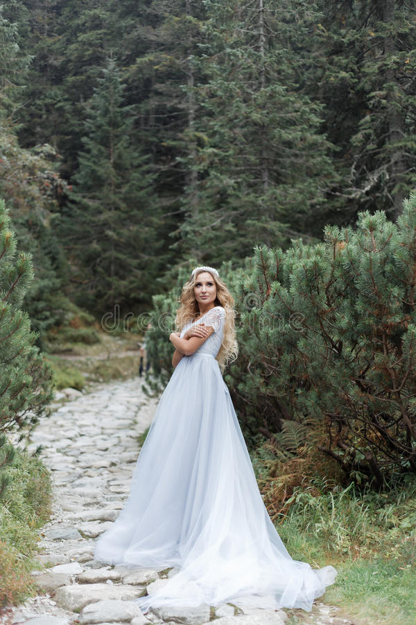 Beautiful gentle girl bride in the air fairy blue wedding dress with luxurious curls in the mountains near the lake with a crown u. Tterly stock photo