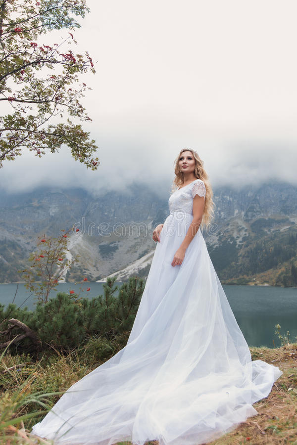 Beautiful gentle girl bride in the air fairy blue wedding dress with luxurious curls in the mountains near the lake with a crown u. Tterly royalty free stock photography