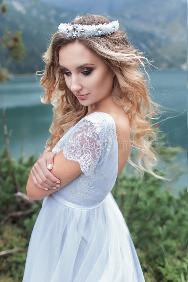 Beautiful gentle girl bride in the air fairy blue wedding dress with luxurious curls in the mountains near the lake with a crown u. Tterly royalty free stock image