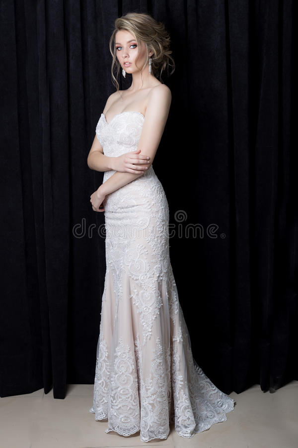 Beautiful gentle girl bride in a beautiful lace dress with a train with evening hairstyle and make-up in the studio on a blac stock photography