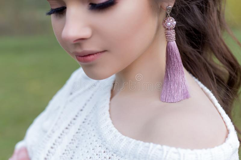 Beautiful gentle girl in a white jacket with fashionable earrings brushes royalty free stock image