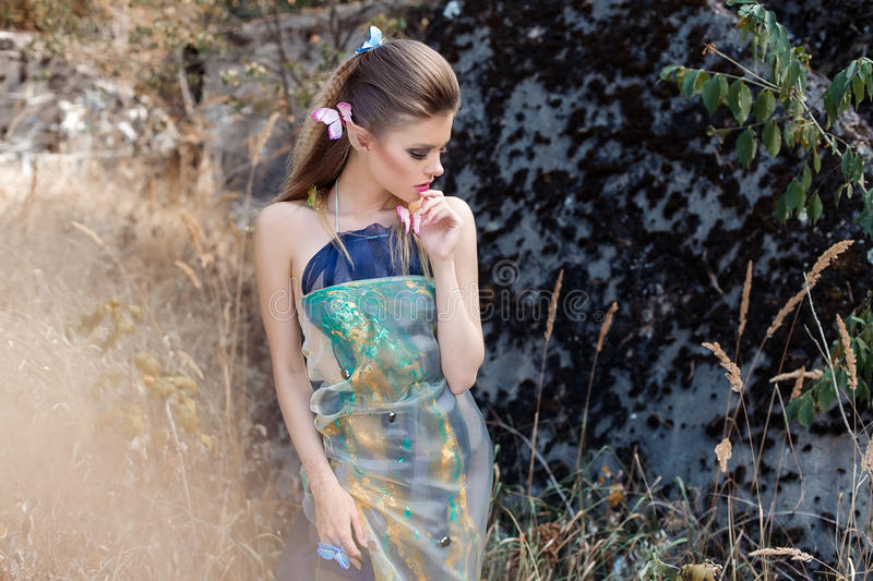Beautiful gentle sweet girl in the fairy tale character in the role of wood elf walking through the forest with butterflies in her royalty free stock image