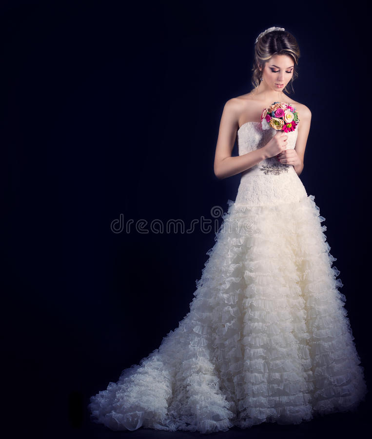 Beautiful gentle woman happy bride in a white wedding dress with a train cabin with a beautiful wedding hairstyle with white royalty free stock photos