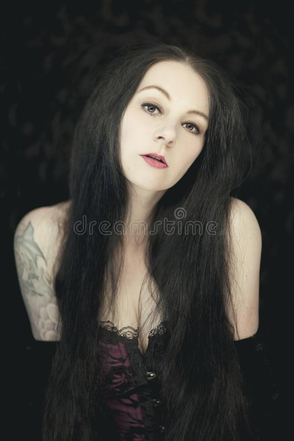 Beautiful german gothic styled woman with shiny long black hair. Looking into camera royalty free stock image
