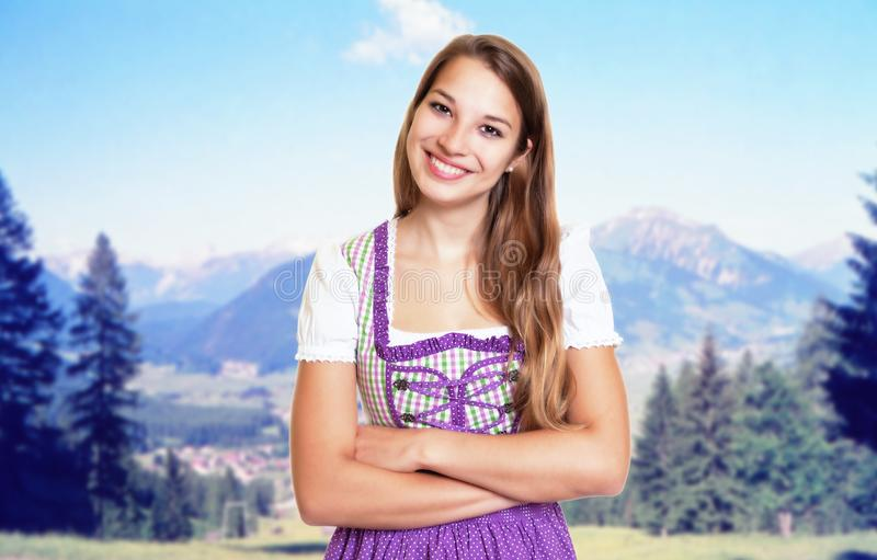 Beautiful german woman in bavarian dirndl with rural landscape. In the background royalty free stock photos