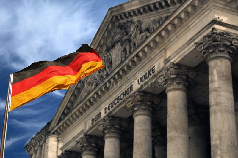 Beautiful  Germany waving flag and behind the famous German Parliament of Berlin Reichstag royalty free stock photography