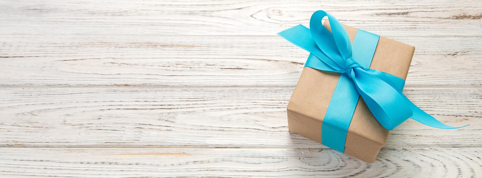 Beautiful gift box with a blue bow on the white wooden table. Top view banner with copy space for you design stock photography