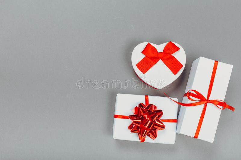 Beautiful gift boxes wrapped in paper with a red ribbon and a bow on a gray surface. stock photos