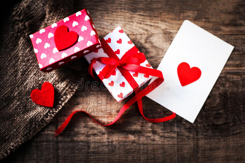 Beautiful Gift boxex with hearts, red bow ribbon and paper heart. On wooden table for Valentines day / holiday concept stock photography