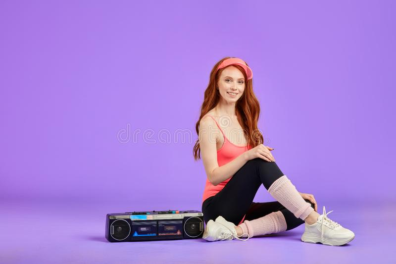 Beautiful ginger girl with glowing skin relaxing after aerobics. Ginger girl with glowing skin and adorable smile, sitting near portable audio cassette player on royalty free stock image