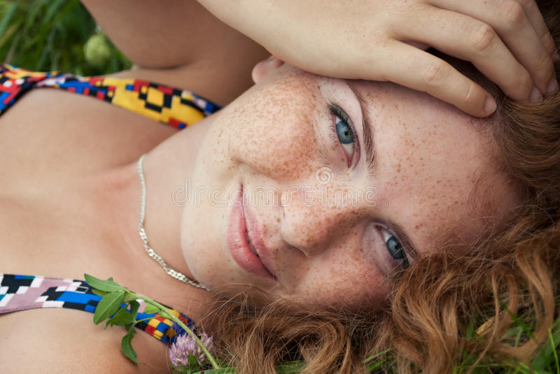 Beautiful ginger girl is lying in the green grass royalty free stock photography