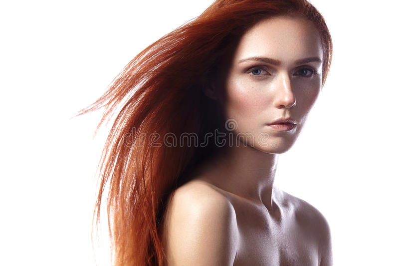 Beautiful ginger young woman with flying hair and naturel makeup. Beauty portrait of model with straight red hair royalty free stock photo