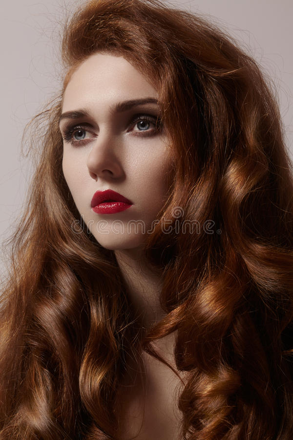 Beautiful ginger young woman with luxury hair style and fashion gloss makeup. Beauty closeup model with red hair. Beautiful ginger young woman with luxury hair royalty free stock images