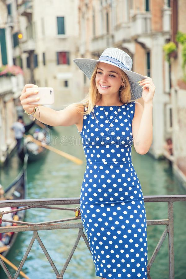 Beautiful gir traveler tourist in blue polka dot dress make selfie in venice Italy. Attractive blonde fashion model young woman. Taking, vacation, gondola royalty free stock photo