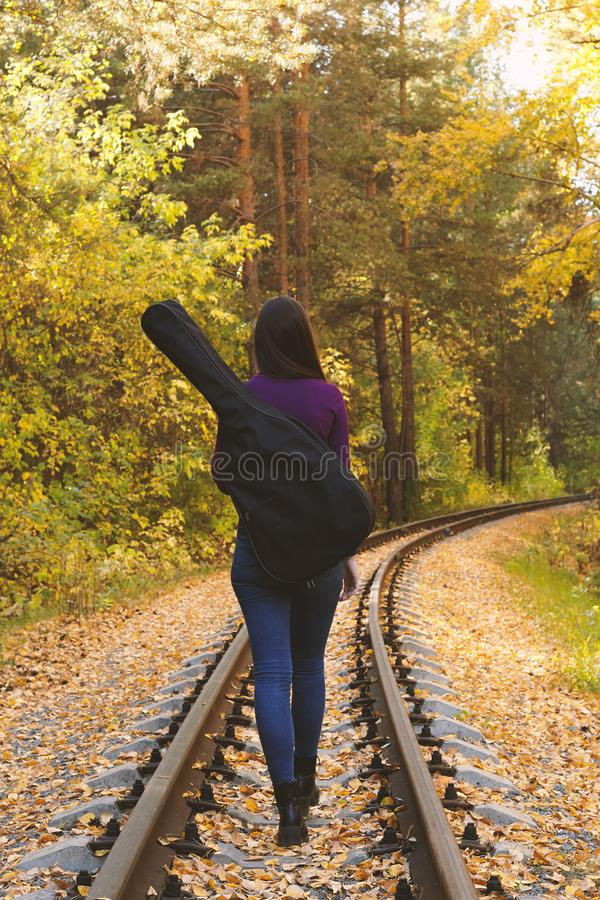 Beautiful girl with acoustic guitar in autumn park royalty free stock photography