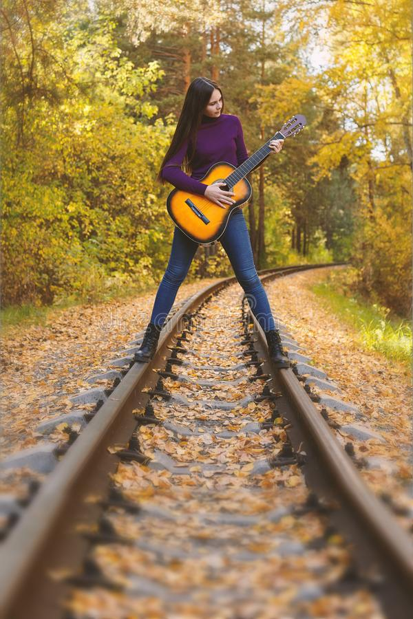 Beautiful girl with acoustic guitar in autumn park stock image