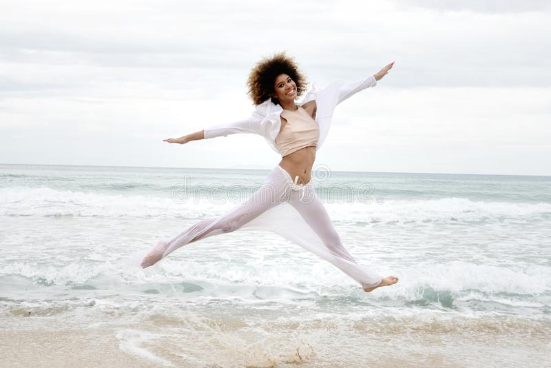 Beautiful girl with afro hair and white dress jump on the beach.  stock photography