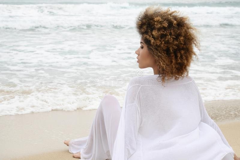 Beautiful girl with afro hair and white dress relax on the beach.  stock image