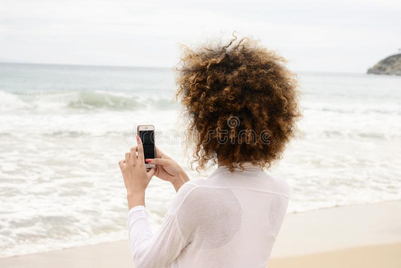 Beautiful girl with afro hair and white dress taking photo with. Smartphone stock photography
