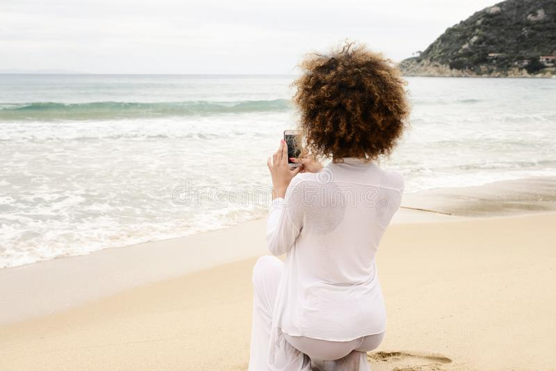 Beautiful girl with afro hair and white dress taking photo with. Smartphone royalty free stock images