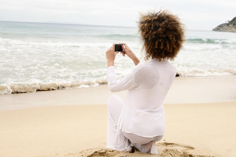Beautiful girl with afro hair and white dress taking photo with. Smartphone stock photo