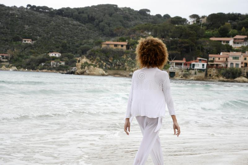 Beautiful girl with afro hair and white dress walk by the sea.  stock images