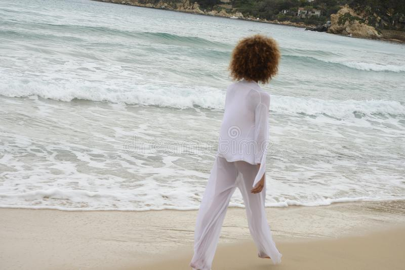 Beautiful girl with afro hair and white dress walk by the sea.  royalty free stock image