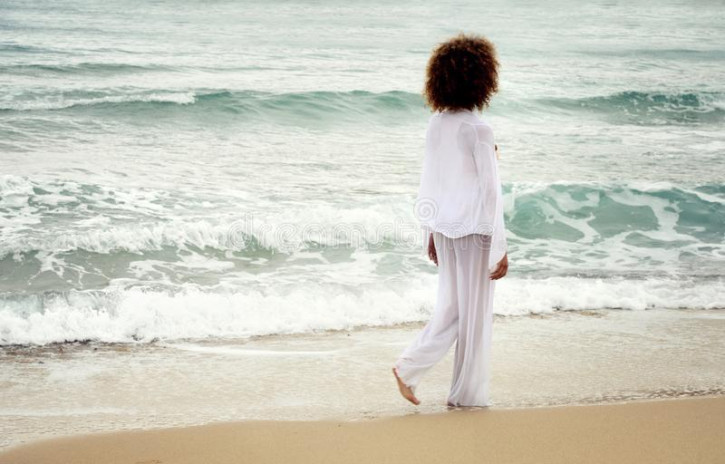 Beautiful girl with afro hair and white dress walk by the sea.  stock photography