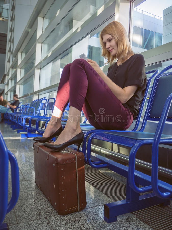 Beautiful girl in the airport terminal with a phone in his hand royalty free stock images