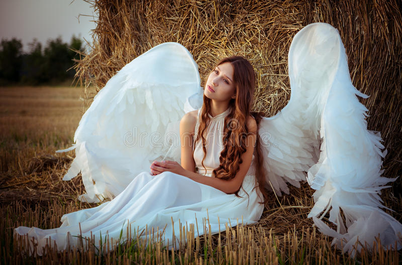 Beautiful girl with angel wings is sitting front of the hay. On the field in the morning stock photos