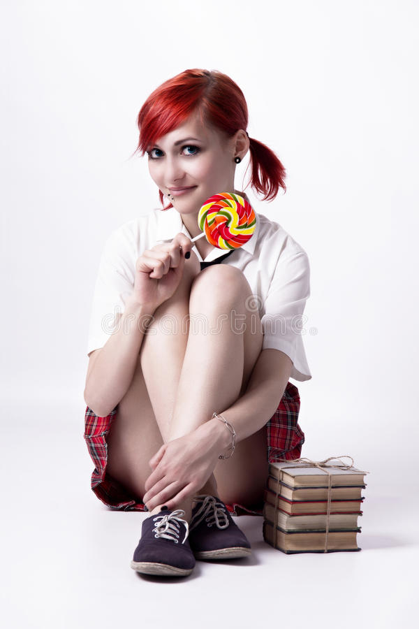 Beautiful girl in anime style with candy. Red-haired girl, image in the style of anime, cheerful face, non-standard, piercings on his face, blue eyes, earrings stock image