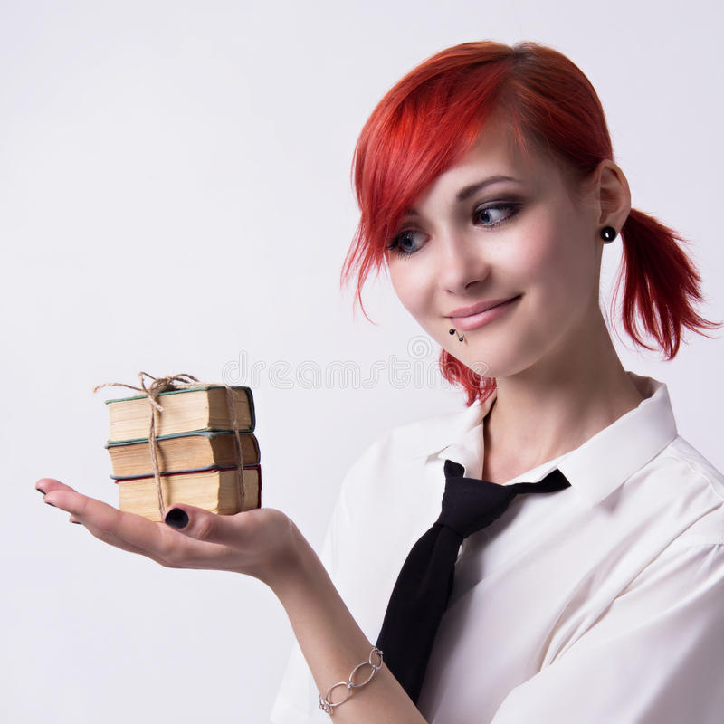 Beautiful girl in anime style with stacks of books. Red-haired girl, image in the style of anime, cheerful face, non-standard, piercings on his face, blue eyes royalty free stock photos
