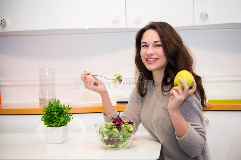 Beautiful girl with an apple and a salad royalty free stock photography