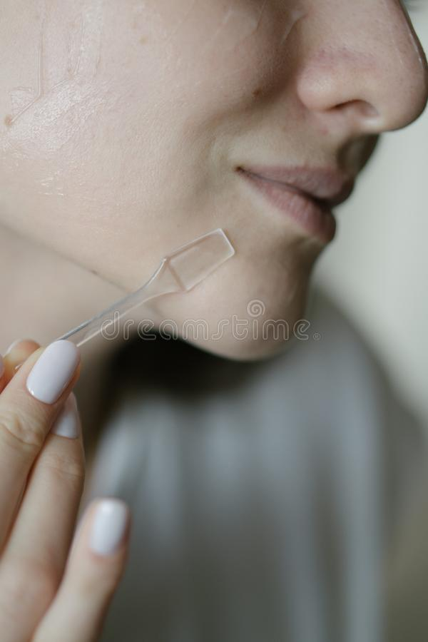 Beautiful girl applies transparent cream on dry clean face skin, chin close-up royalty free stock photo