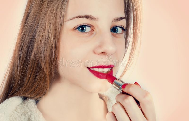 A beautiful girl is applying lipstick to her lips royalty free stock image