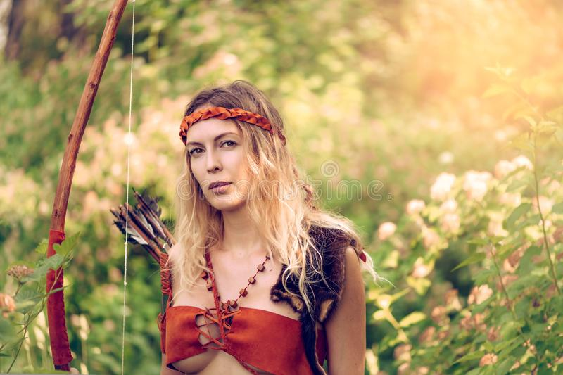 Beautiful girl archer with long blond hair with a bow and arrows dressed in leather royalty free stock photography