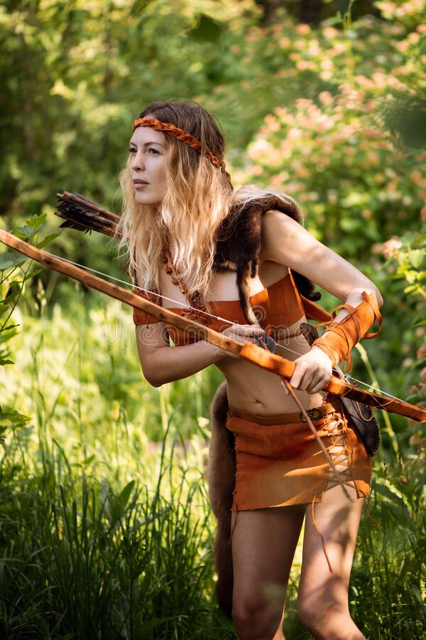 Beautiful girl archer with long blond hair with a bow and arrows dressed in leather stock photo