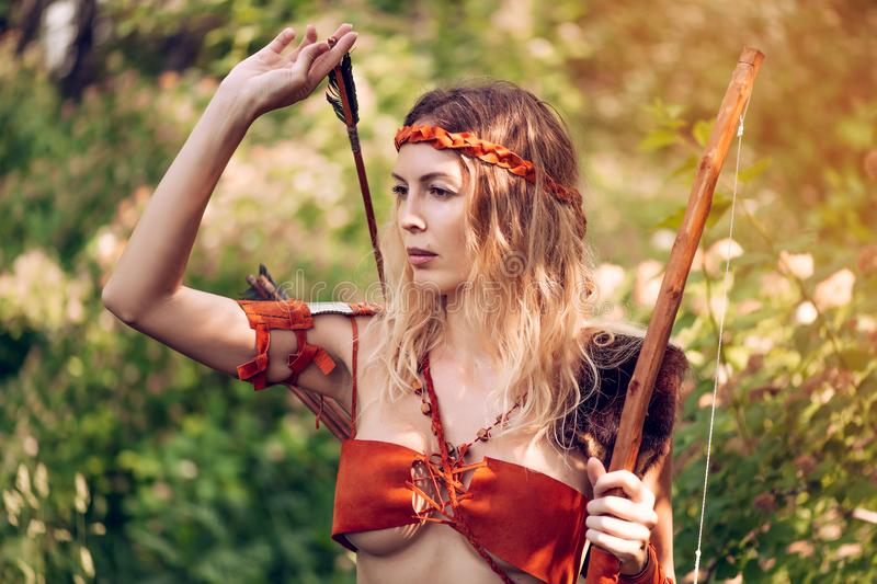 Beautiful girl archer with long blond hair with a bow and arrows dressed in leather. And wristwear pulls an arrow out of the quiver royalty free stock image