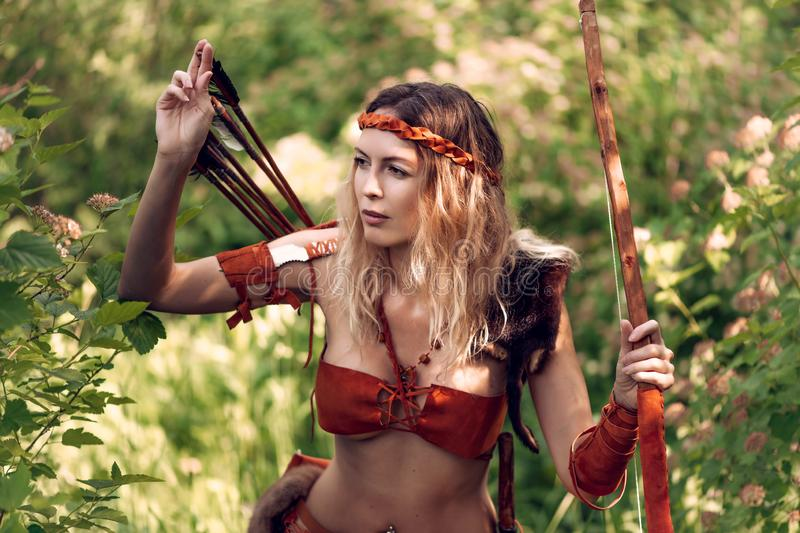 Beautiful girl archer with long blond hair with a bow and arrows dressed in leather. And wristwear pulls an arrow out of the quiver royalty free stock photography