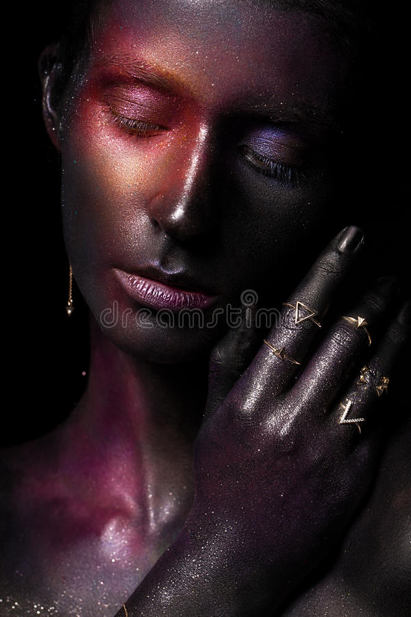 Beautiful girl with art space makeup on her face and body. Glitter Face. Photo taken in the studio stock image