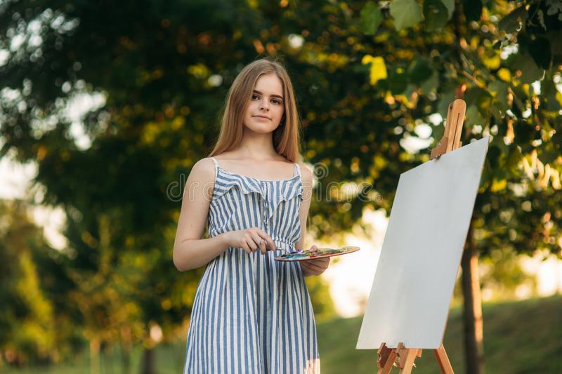 Beautiful girl artist is standing in the park and holding palette with paints royalty free stock photo