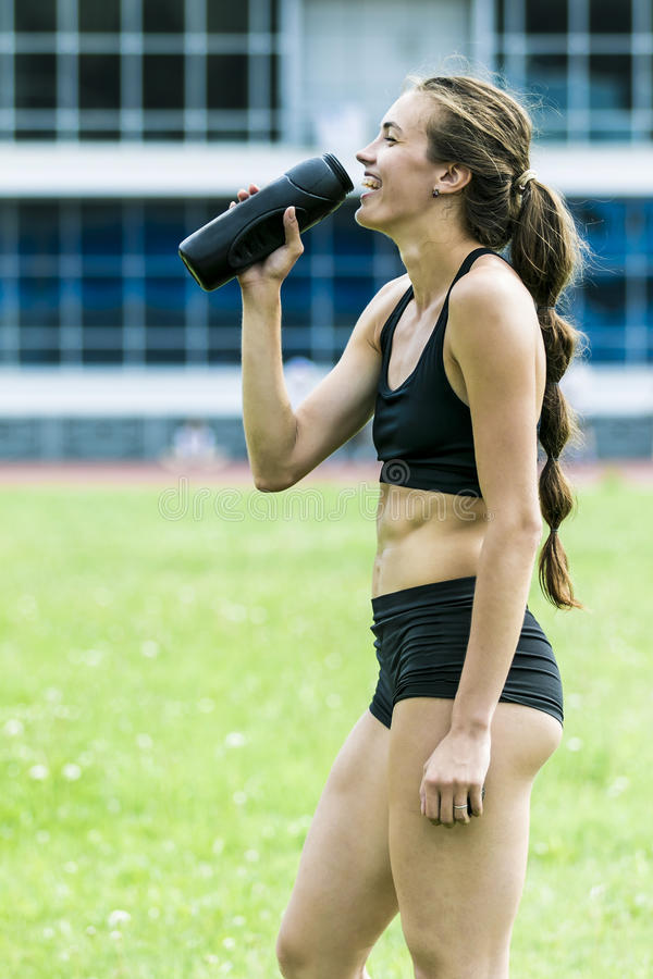 Beautiful girl athlete drinking water stock photography