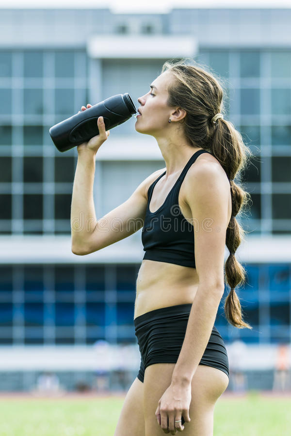Beautiful girl athlete drinking water stock images