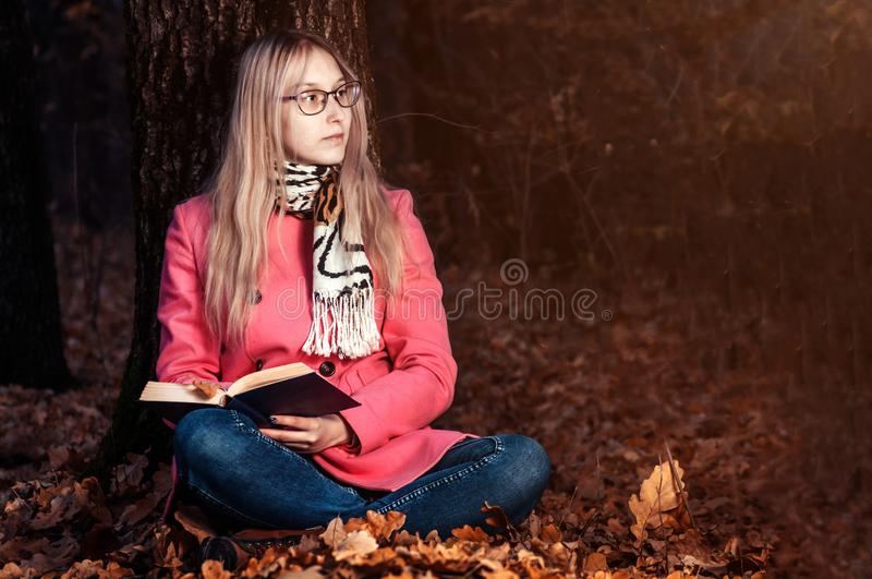 Beautiful girl in autumn forest reading a book. woman sits near a tree and holds a book royalty free stock image