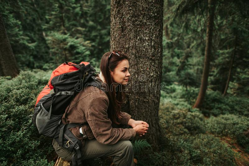 Beautiful girl with backpack sitting on tree trunk in forest royalty free stock photo