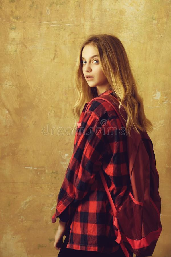 Beautiful girl with backpack in stylish red checkered shirt stock image