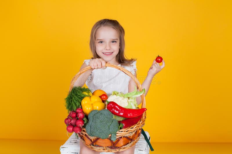 Beautiful girl with a basket of fresh vegetables, radishes, broccoli, tomato pepper stock photos