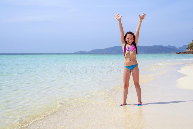 Happy child with hands up against the ocean with copy space. Concept of sunny and happy summer stock photography