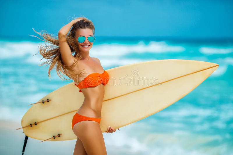 Beautiful girl on beach with surfboard stock photos