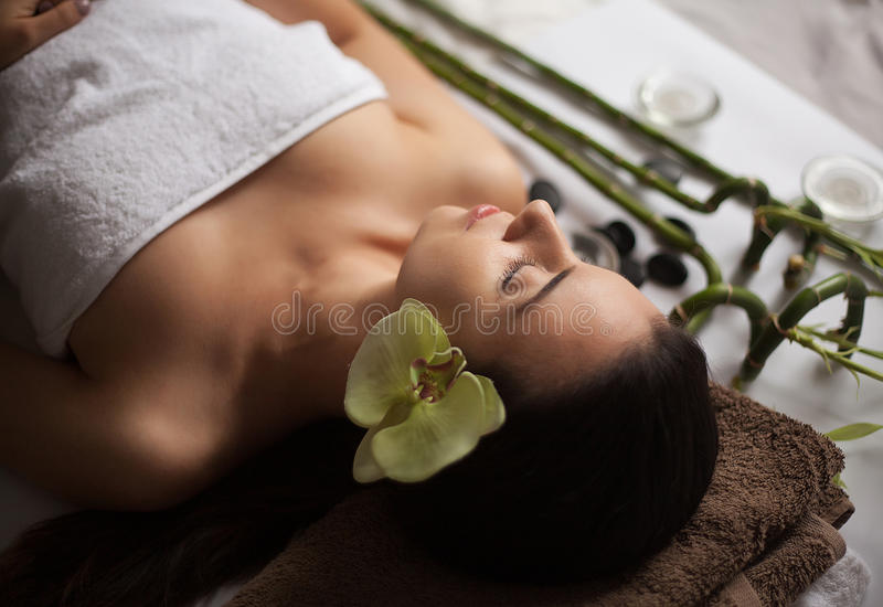 Beautiful girl in a beauty salon with orchid flower in her hair. spa treatments. close-up royalty free stock photos